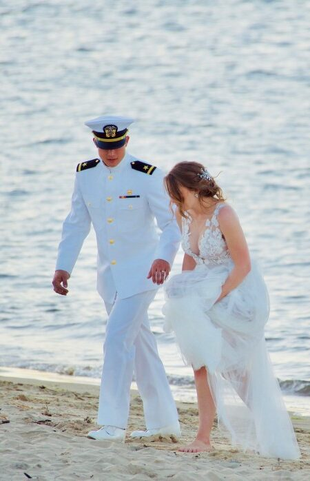 beautiful-scene-of-a-navy-man-in-uniform-walking-with-his-bride-on-the-sand-by-the-seashore_t20_bxNXXm
